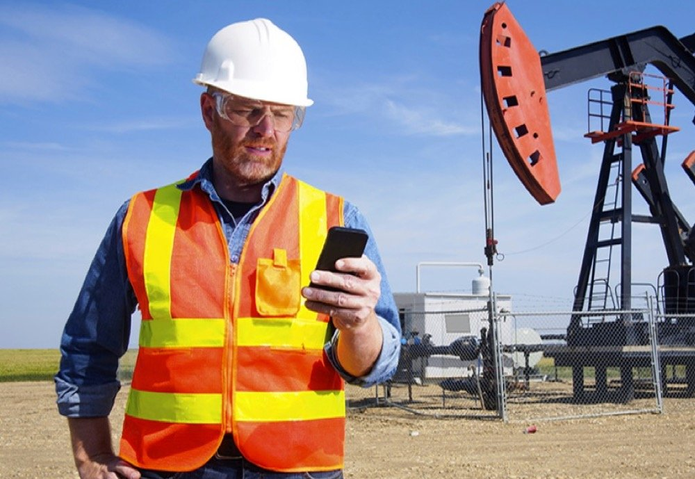 oil worker on smartphone cropped.jpg