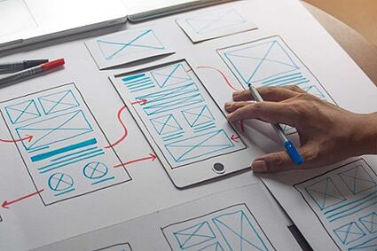 A UI designer working on mobile app development plans